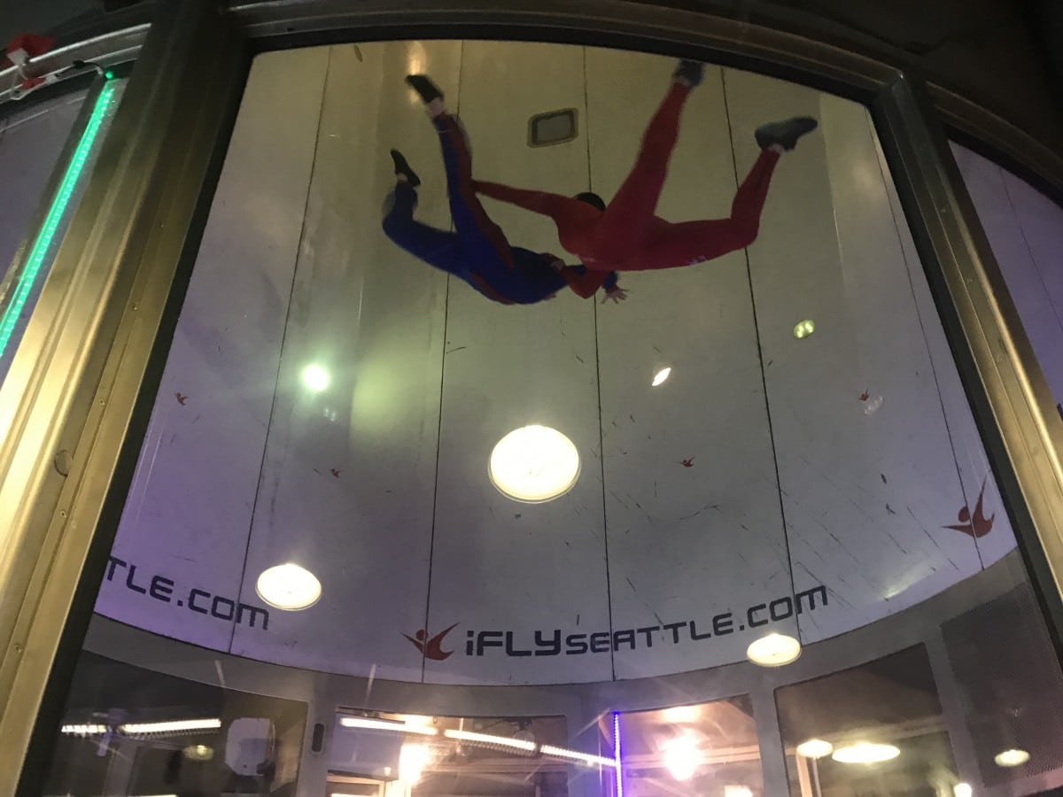 Two indoor skydivers floating high in the wind tunnel.
