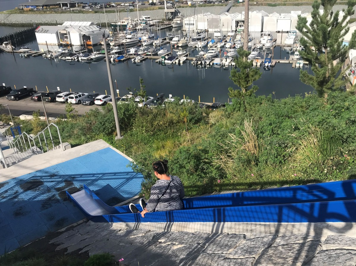 A woman goes down a slide at Tacoma's Dune Park